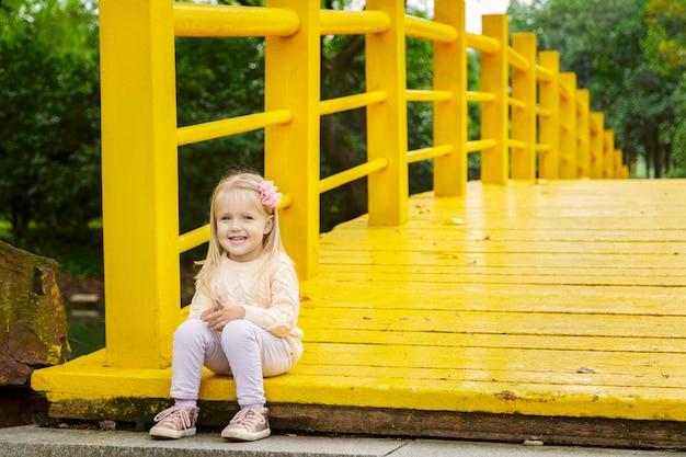 Chica de llittle con estilo en un puente amarillo en el parque