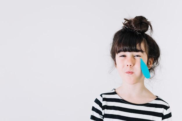 Chica llorando con lágrimas de papel
