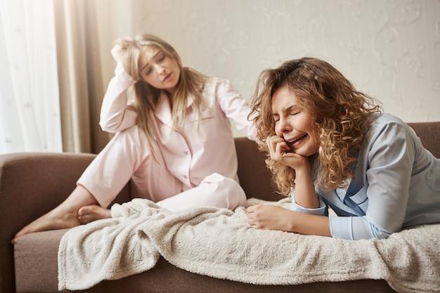 Chica llorando de su soledad sin pareja. hermosa rubia europea en ropa de dormir sentada en el sofá, acariciando a su triste y miserable novia con el cabello rizado, tratando de calmarla y animarla