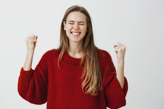 Chica logró objetivos, feliz de finalmente ganar el concurso. satisfecho triunfante joven en suéter rojo suelto, levantando los puños y cerrando los ojos, celebrando la victoria y gana