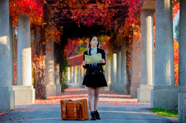 Chica con maleta y mapa en callejón de uvas rojas