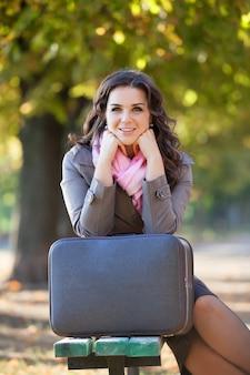 Chica con maleta en otoño al aire libre.