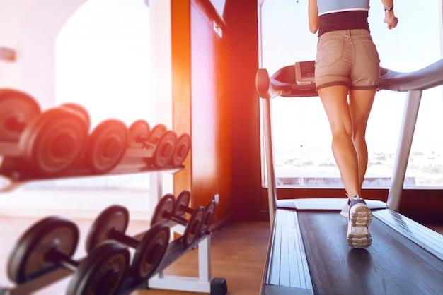Chica en la mañana correr en la cinta en el gimnasio frente a una gran ventana en el fondo del mar