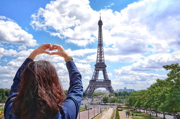 Chica en la mano muestra de corazón con camisa de jean en vacaciones de verano en el cielo y la torre eiffel en el fondo en parís