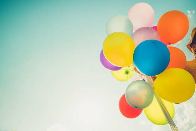 Chica mano sosteniendo globos multicolores