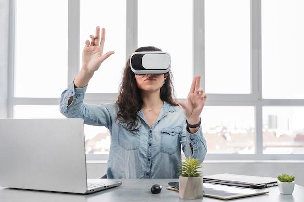 Chica con las manos en alto usando las gafas de realidad virtual