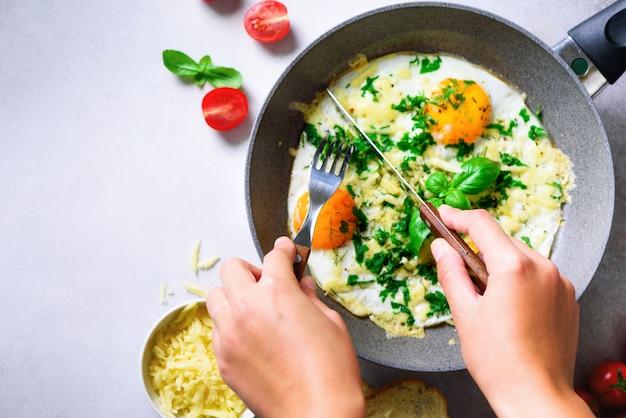 Chica manos arriba sartén con tres huevos cocidos, hierbas, queso, tomates