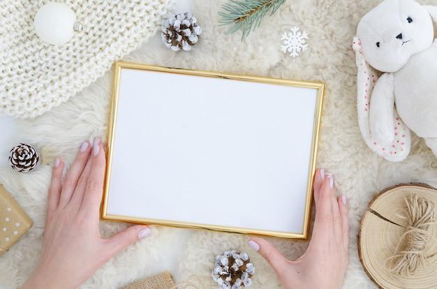 Chica manos sostiene marco de fotos de oro maqueta navidad, año nuevo fondo
