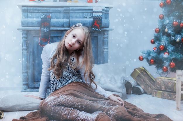Chica una manta nevada en el árbol de navidad.