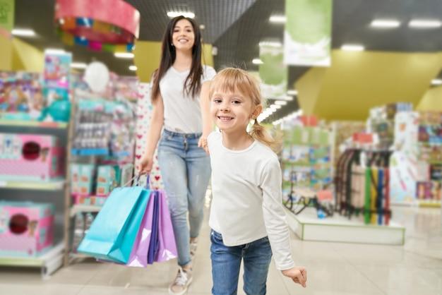 Chica manteniendo la mano de mamá y corriendo hacia adelante en juguetería