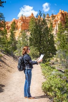 Chica con mapa en un entorno natural.