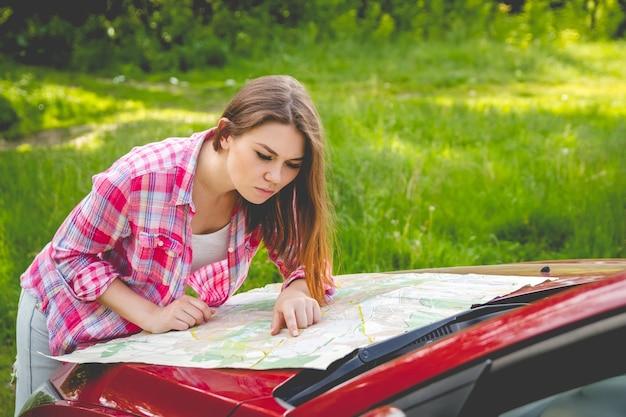 Chica con mapa en mano de pie junto a un coche en el bosque.