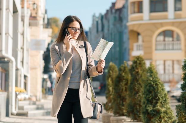 Chica con mapa turístico hablando por teléfono móvil