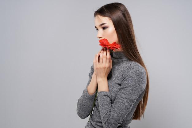 Chica con maquillaje brillante estudio de lujo de romance de flor roja
