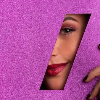 Chica con maquillaje brillante, lápiz labial rojo mirando a través del agujero en pape violeta