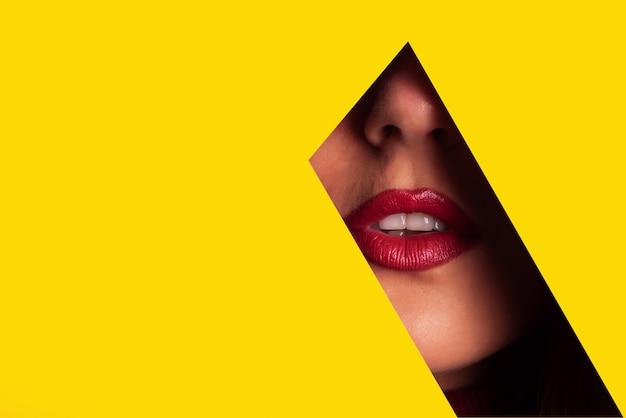 Chica con maquillaje brillante, lápiz labial rojo mirando a través del orificio en papel amarillo