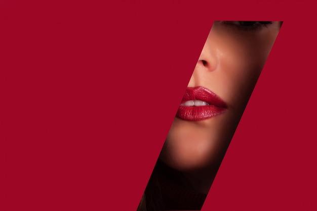Chica con maquillaje brillante, lápiz labial rojo mirando a través del orificio en papel