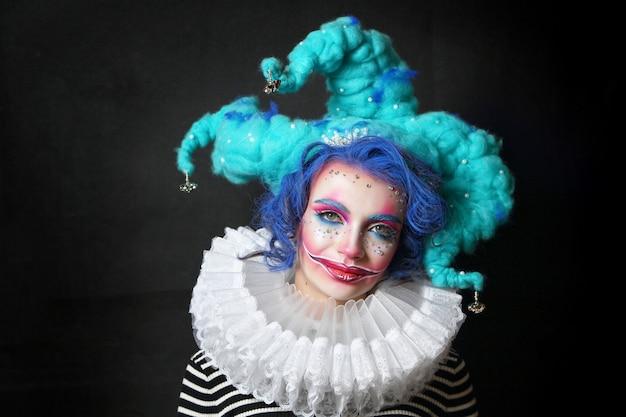 Chica en maquillaje y disfraz de bufón