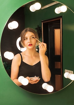 Chica maquillándose en una habitación verde
