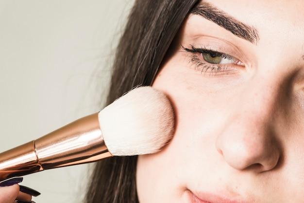 Chica maquillándose las mejillas