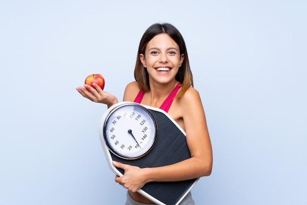 Chica con máquina de pesaje sobre azul aislado con máquina de pesaje y con una manzana