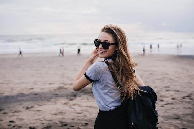 Chica maravillosa en gafas de sol negras mirando por encima del hombro mientras está de pie en la playa de arena. foto de hermosa modelo femenina con blackpack posando en la naturaleza.