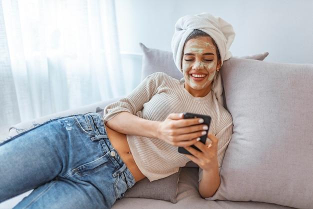 Chica con máscara de belleza relajante en casa, mensajes de texto por teléfono celular