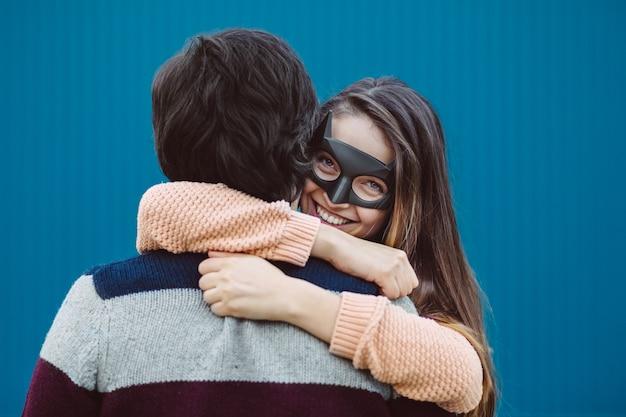Chica con una máscara besando a su chico joven.
