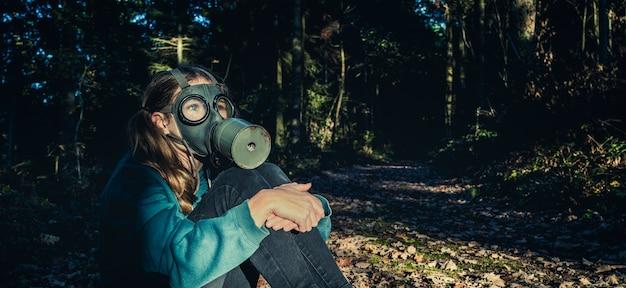 Chica con máscara de gas en el bosque al atardecer