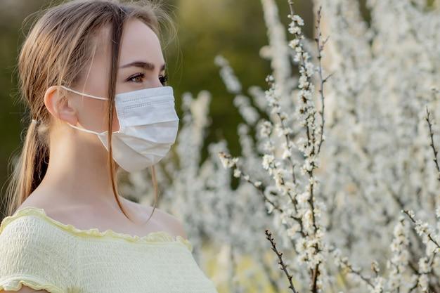 Chica con una máscara médica. chica en la primavera entre el jardín floreciente. una niña en una máscara médica protectora. concepto de alergia de primavera