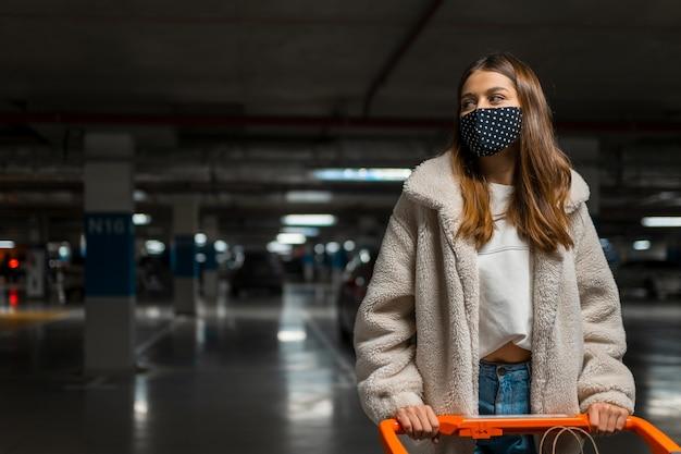 Chica en máscara médica en el estacionamiento subterráneo del centro comercial