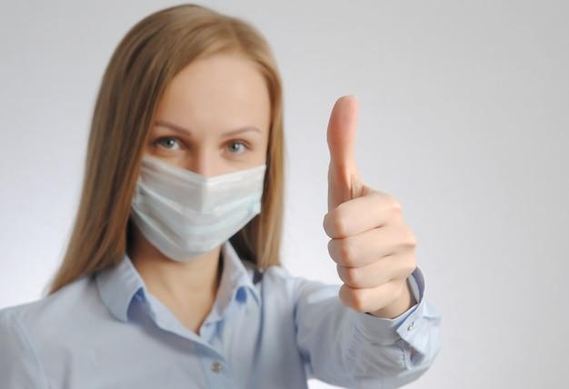 Chica con máscara médica muestra el pulgar hacia arriba