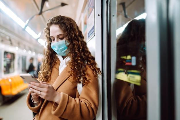 Chica en máscara médica protectora estéril en su rostro con un teléfono en un vagón de metro. mujer que usa el teléfono para buscar noticias sobre coronavirus. el concepto de prevenir la propagación de la epidemia.