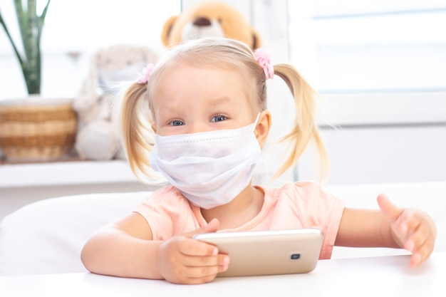 Chica con una máscara médica protectora que usa un teléfono móvil, un teléfono inteligente para realizar videollamadas, habla con familiares, una niña se sienta en su casa, la cámara web de la computadora en línea, hace una videollamada.