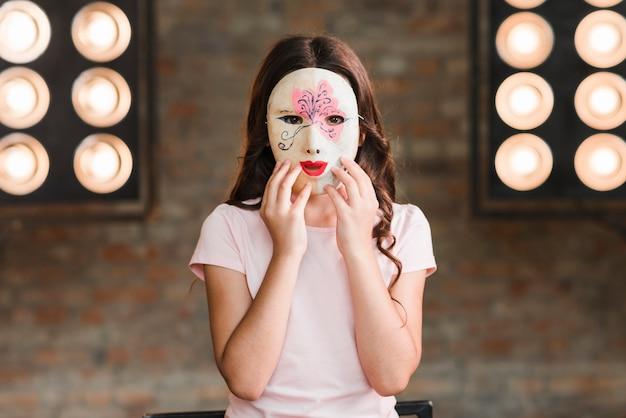 Chica con máscara de pie contra la luz de la etapa