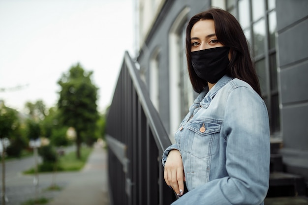 Chica en una máscara protectora en un balcón mira una ciudad vacía