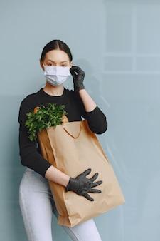 Chica con máscara protectora sostiene paquete con productos
