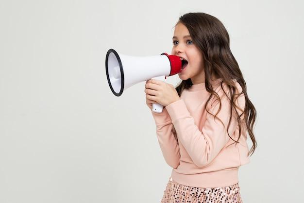 Chica con un megáfono en mano hacia los lados en una pared de estudio blanco con espacio en blanco