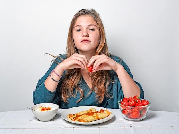 Chica en la mesa del desayuno comiendo panqueques y fresas