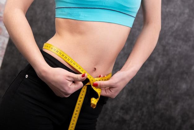 Chica mide su cintura con un tipo de medición. de cerca