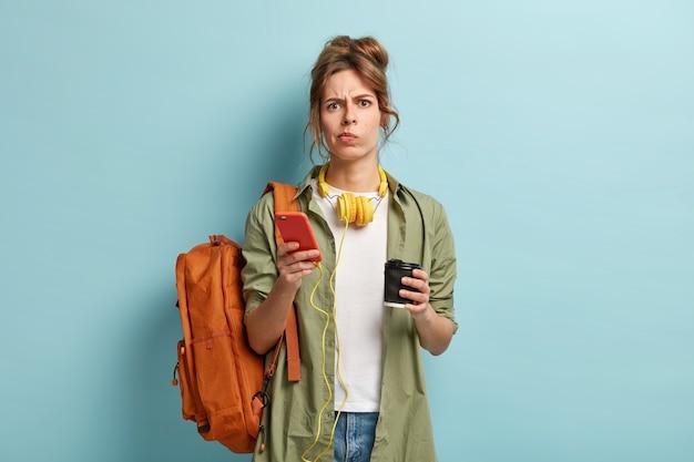 Chica milenaria cansada frustrada bebe café para llevar, sostiene un dispositivo de teléfono inteligente conectado a los auriculares, disfruta de la lista de reproducción