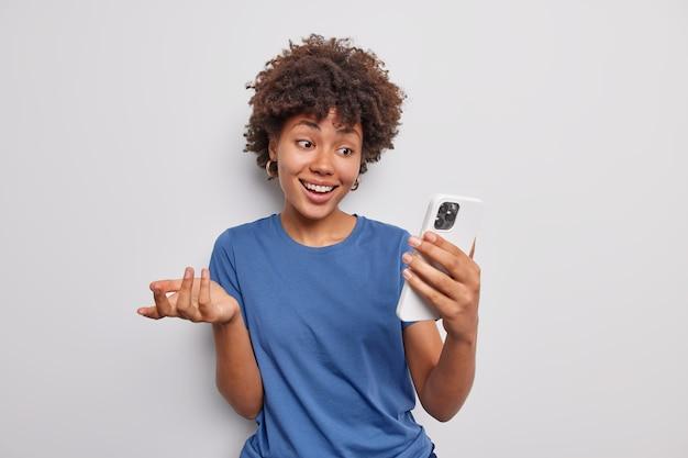 Chica milenaria positiva hace videollamada se comunica con su mejor amigo sostiene a distancia el teléfono móvil utiliza conexión gratuita a internet vestida con una camiseta azul informal aislada sobre fondo blanco