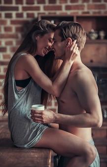 La chica mira al chico y lo abraza mientras está sentado en la mesa de la cocina. pareja abrazándose en la cocina en la mesa.