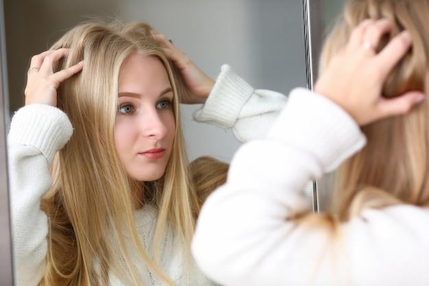 Chica mira espejo en la reflexión, alisa el cabello.