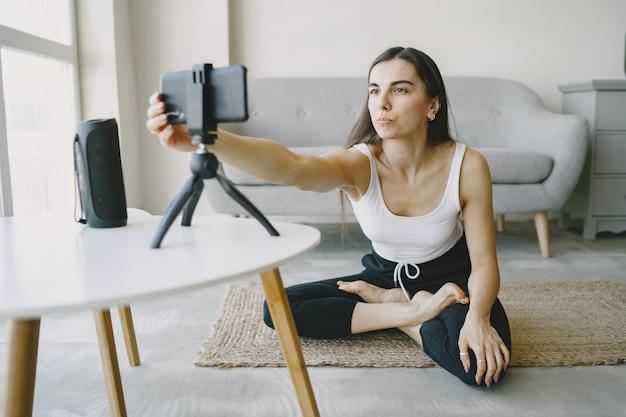 Chica mira el teléfono con cámara. comunicación online. entrenamiento en video