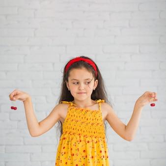 Chica mirando cerezas rojas sosteniendo en sus manos