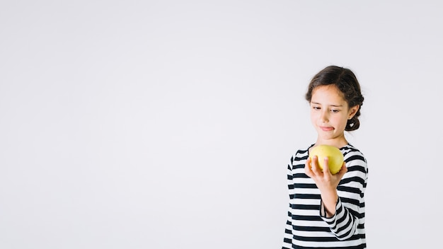Chica mirando la manzana con disgusto