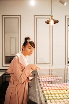 Chica mirando pasteles a través del escaparate de cristal en el café.