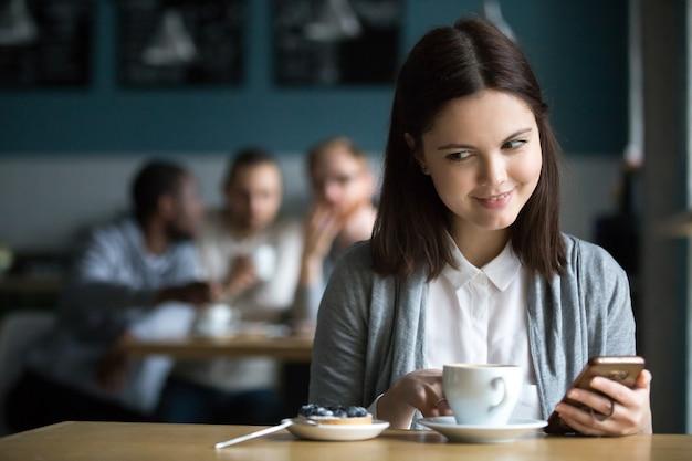 Chica mirando postre ordenado por chicos coqueteando en café