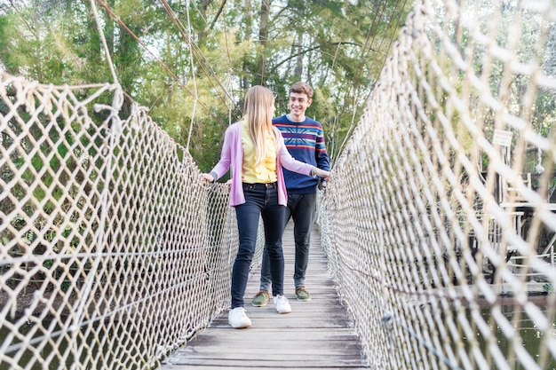 Chica mirando a su novio mientras cruzan el puente